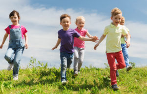 54443941 - summer, childhood, leisure and people concept - group of happy kids playing tag game and running on green field outdoors